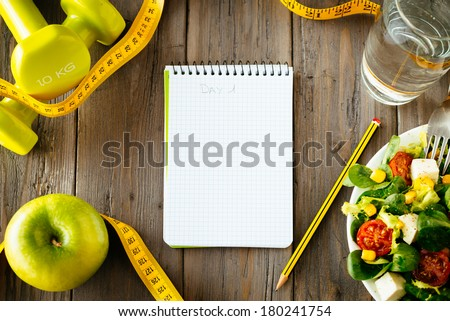 Workout and fitness dieting copy space diary. Healthy lifestyle concept. Salad, apple, dumbbell, water and measuring tape on rustic wooden table. - stock photo