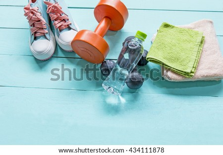 Workout and fitness dieting- Healthy lifestyle concept and other stuff Dumbbell, water,stereo speaker on the blue wooden background - stock photo