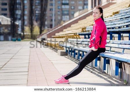 Workout and health! Young attractive girl in a sports clothing is resting after a workout. Makes workout and stretching on the street the stadium in the afternoon. - stock photo