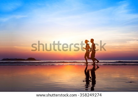workout background, two people jogging on the beach at sunset, runners silhouettes, healthy lifestyle concept