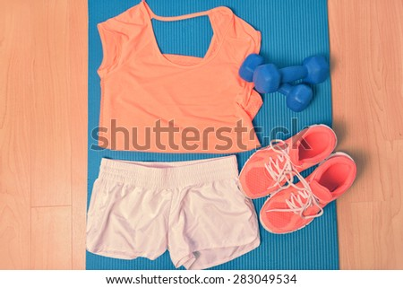 Workout clothes - fitness outfit and running shoes. Overhead of clothing ready for lifting weights at the gym or at home, laying on a yoga mat on the floor. Matching orange t-shirt and sneakers. - stock photo