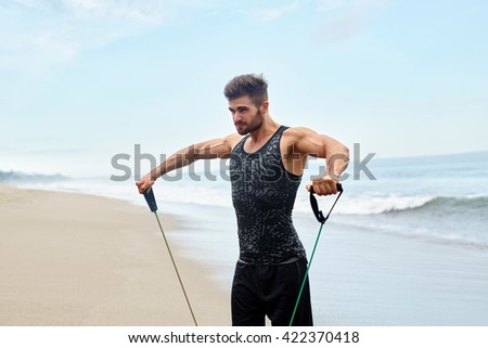 Workout Exercise. Portrait Of Healthy Handsome Active Man With Fit Muscular Body Doing Expander Stretching Exercises, Exercising At Beach. Sporty Male Training Outdoor. Sports And Fitness Concept - stock photo