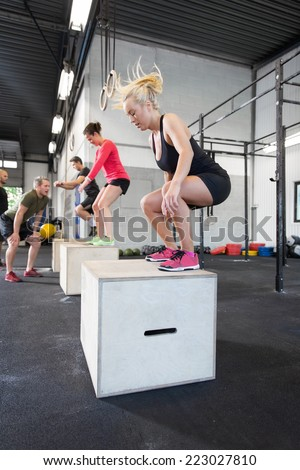 Workout group trains box jumps at the fitness gym - stock photo