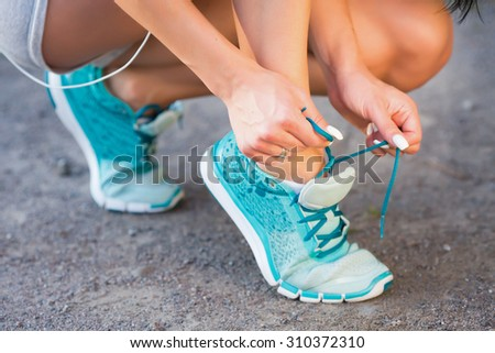 Workout in a park. Young sporty woman tying blue running shoe laces before jogging in park on beautiful summer day, close up - stock photo
