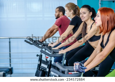 Workout in the gym. Athletic girl pedaling and looking at the camera on a stationary bike at the gym while her girlfriend athletes pedaled on bicycles in the background - stock photo