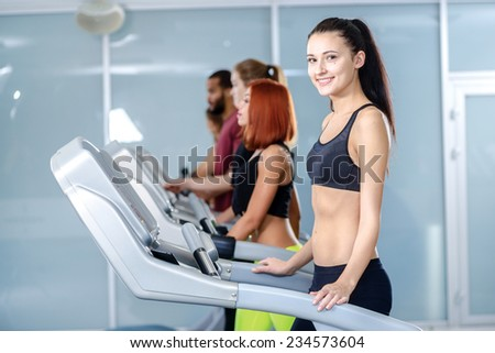Workout in the gym. Sport and slender girl running on a treadmill and looking at the camera and smiling. Athlete dressed in sports uniforms and running in the gym. - stock photo