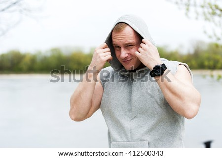 Workout man in hood resting by the river outdoor.
