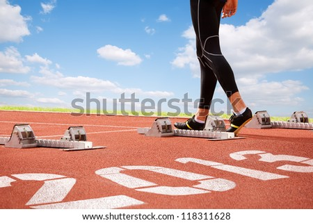 Workout of athlete on start line of cinder-track with numerals of new year on sky background. - stock photo