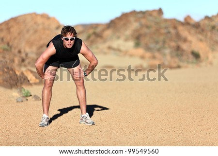 Workout outdoor runner. Man running taking a break from run outside in beautiful desert landscape. Fit young caucausian athletic model training for marathon outdoors. - stock photo