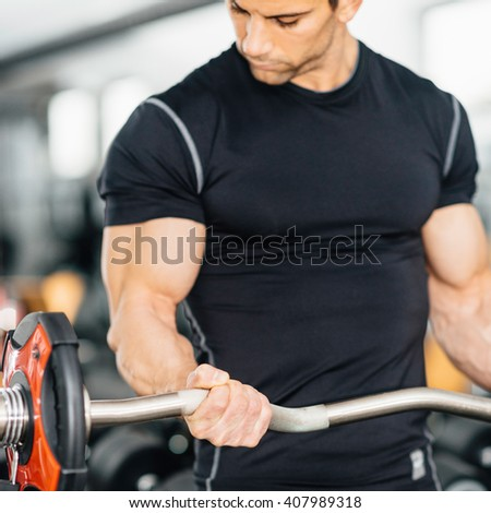 Workout with barbell weights - Muscular young man exercising in gym - stock photo