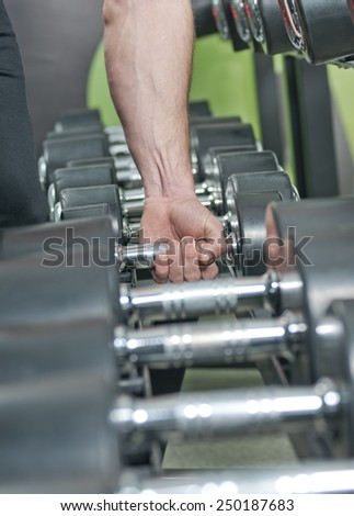 Workout with dumbbells at gym.