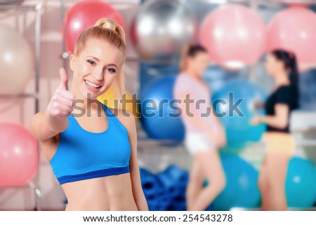 Workouts keep me in good mood. Beautiful young woman in sports clothing smiling and showing her thumb up while standing on the background of two woman in the gym - stock photo