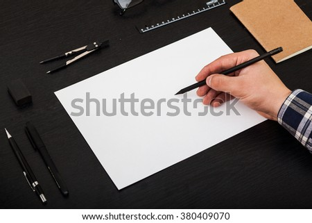 Workplace for artist, drawing on a4, black table - stock photo