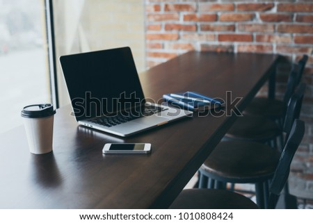 Workplace in a cafe. Freelancer works on a laptop in a cafe with a cup of coffee.