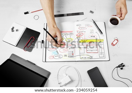 Workplace. Man working on notepad with hand drawn website project.  - stock photo