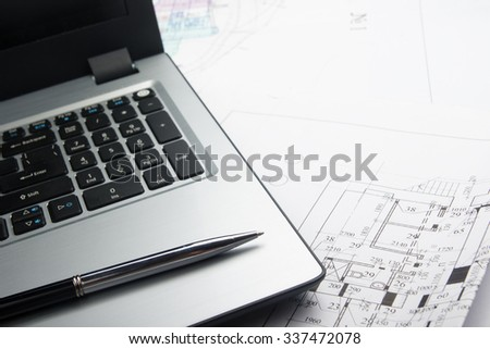 Workplace of architect - Architectural project, blueprints, blueprint rolls on laptop, pen on plans. Engineering tools. Construction background.