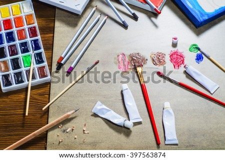 Workplace of designer, artist, painter, top view. Accessories to drawing: canvas, paints, brushes, pencils, flat lay. Working artist tools, mixing paints, creative. - stock photo