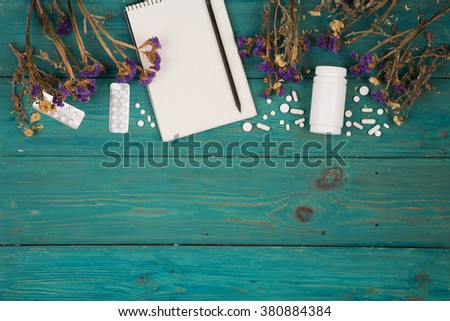 Workplace of doctor - medicine clipboard, bottle, flower and pils on wooden desk - stock photo