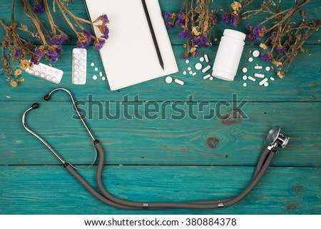 Workplace of doctor - stethoscope, medicine clipboard, bottle, flower and pils on wooden desk - stock photo