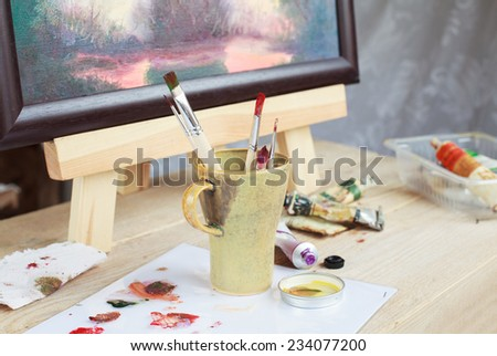 Workplace of the artist who paints a picture of the landscape using oily paints mounted on an easel. Selective focus on brush - stock photo