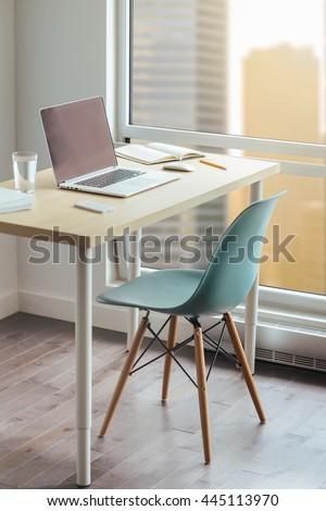 Workplace photographer, Modern desktop in loft, Wooden desk with modern chair, Desktop with modern laptop, glass of water, modern smartphone, notebook. View of downtown, Sunrise, Shallow DOF. - stock photo