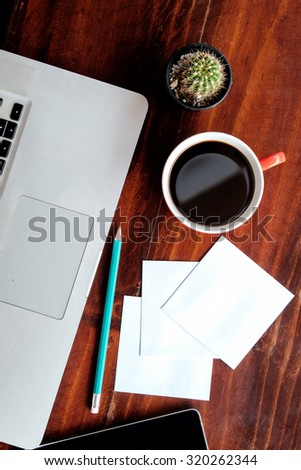 Workplace, Smart phone notebook and coffee red cup on wood table - stock photo