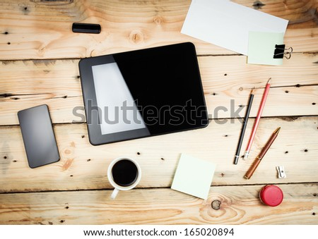 Workplace, tablet pc and smart phoned on wooden table - stock photo