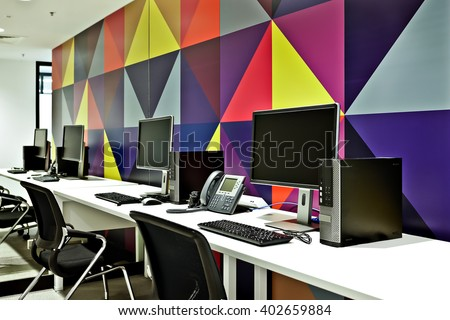 Workplace with computers, chairs and tables including telephones in front of a colorful wall design art - stock photo