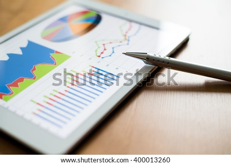 Workplace with digital tablet showing charts and diagram - stock photo