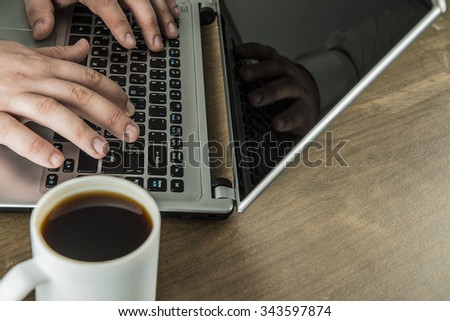 Workplace with hands on keyboards of laptop, white cup of coffee on brown wooden table background. Above view shot. Empty copy space for inscription or objects. - stock photo