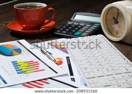 Workplace with keyboard cup of coffee and graphs - stock photo
