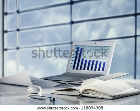 Workplace with laptop, mouse and notepad - stock photo