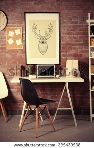 Workplace with laptop, table and bookcase brick wall background - stock photo