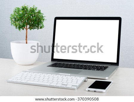 Workplace with modern gadgets. Laptop on a table with blank screen - stock photo