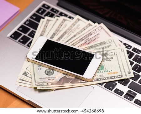 Workplace with money and electronic devices - cellphone and laptop computer. Mobile phone and US dollar banknotes on keyboard of notebook. Concept of payment and savings. - stock photo