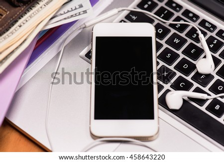Workplace with money and electronic devices - cellphone, headphones for music and laptop computer. Mobile phone and US dollar banknotes on keyboard of notebook. Concept of payment and savings.