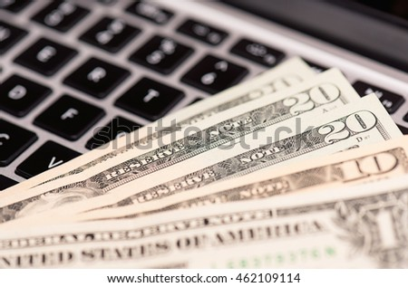 Workplace with money and notebook - US dollar banknotes on keyboard of laptop computer.