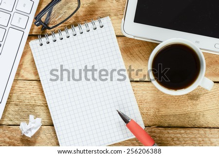 Workplace with notebook and coffee. Workplace with keyboard , tablet pc , coffee, notebook with pen on wood table - stock photo