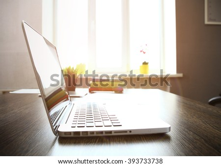 Workplace with open laptop with black screen on modern wooden desk, angled notebook on table, filtered image, focus on keyboard - stock photo
