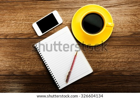 Workplace with phone,notebook, pen and cup of coffee on work table top view - stock photo