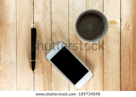 Workplace with phone , pen and a cup of coffee on a wooden work table top view - stock photo