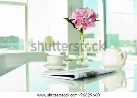 Workplace with porcelain cup and pot, newspaper and bunch of flowers - stock photo