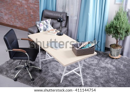 Workplace with table, office chair and laptop in living room - stock photo
