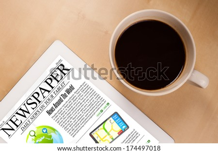 Workplace with tablet pc showing news and a cup of coffee on a wooden work table close-up
