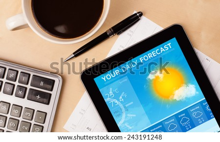 Workplace with tablet pc showing weather forecast and a cup of coffee on a wooden work table close-up - stock photo