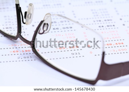 Worksheets or reports showing red figures through eye glasses