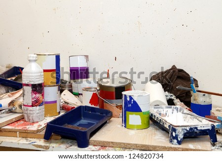 Workshop with different paint cans and other painting equipment - stock photo