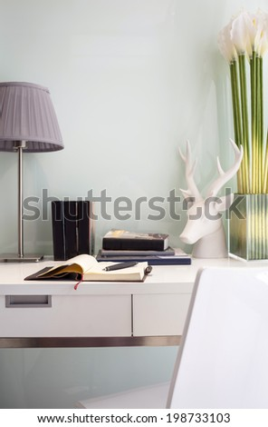 Workspace table with book lamp and chair decorate with flower.The modern style home office.