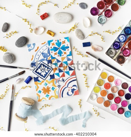 Workspace. Tiles painted with watercolor on paper, spool with blue ribbon, yellow mimosa, stones, brushes isolated on white background. Flat lay, overhead view, top view - stock photo