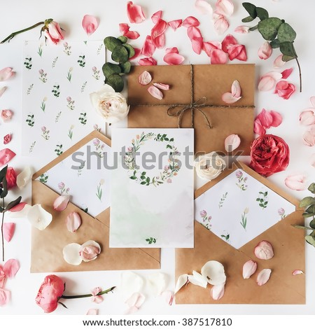Workspace. Wedding invitation cards, craft envelopes, pink and red roses and green leaves on white background. Overhead view. Flat lay, top view - stock photo